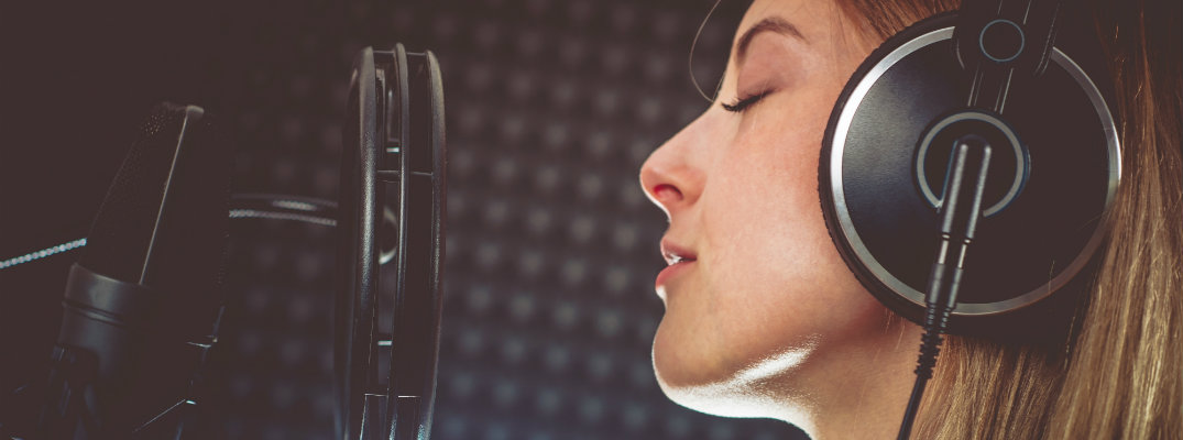 woman in a sound recording room singing into a microphone with her headphones on