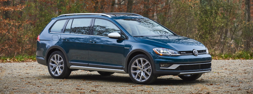 2018 Volkswagen Golf Alltrack Silk Blue Metallic paint color exterior shot parked on a dirt gravel parking lot within a fall forest with falling leaves