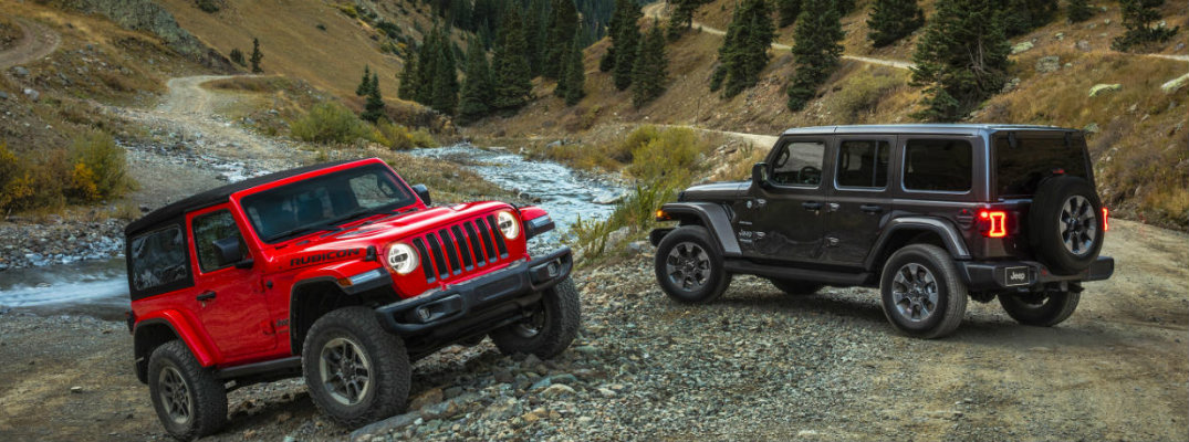 Two 2018 Jeep Wrangler models parked on back country terrain with stream and trees in background