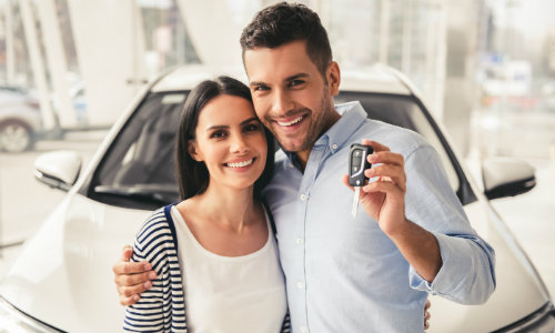Couple posing in front of a car with keys in the man's hand
