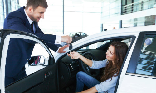 Man in dealership handing keys to woman sitting in car