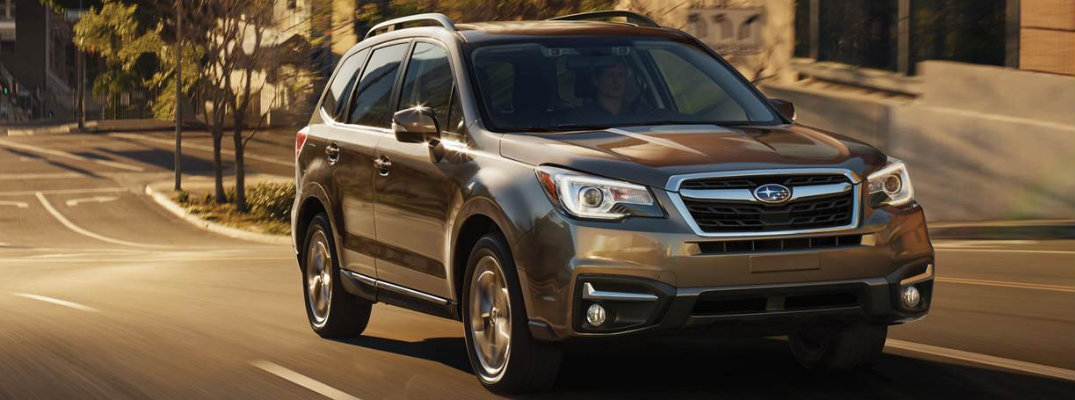 2018 Subaru Forester driving down empty city street at dusk