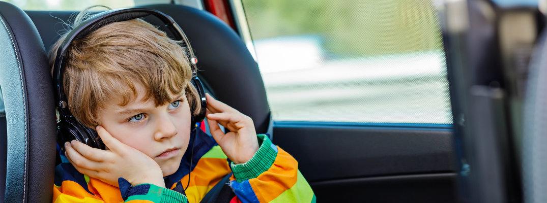 Toddler wearing brightly colored jacket and listening to music through headphones in car