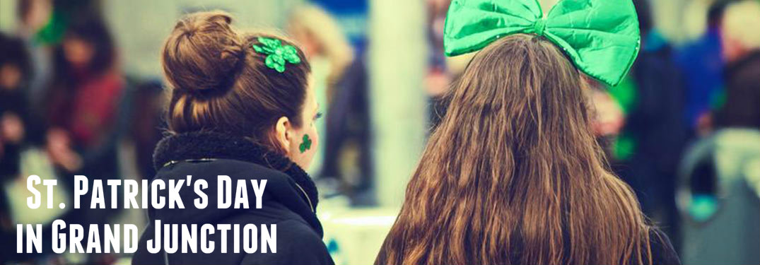 "Two girls wearing bows in St. Patrick's Day parade with ""St. Patrick's Day in Grand Junction"" written in frame"