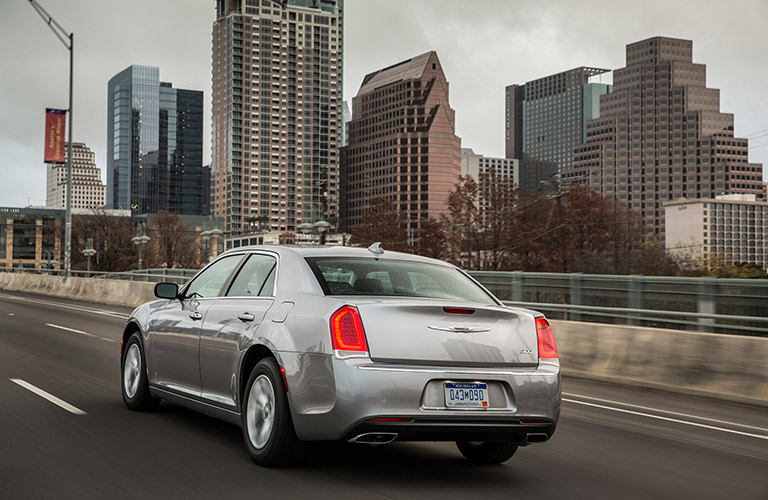 Rear view of silver 2018 Chrysler 300 driving with city skyline in background