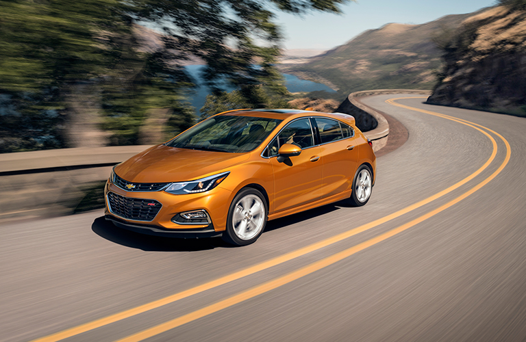 Orange Chevrolet Cruze driving down winding road