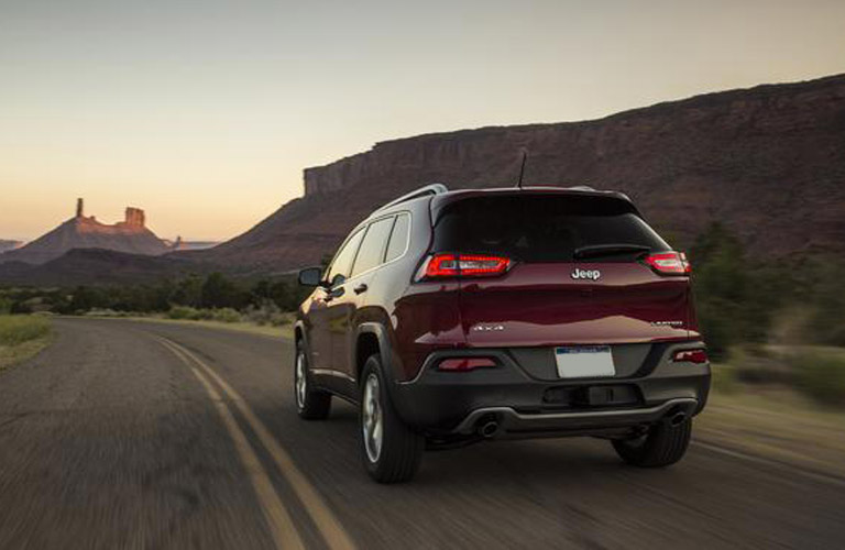 Rear view of red 2018 Jeep Cherokee driving on road at sundown