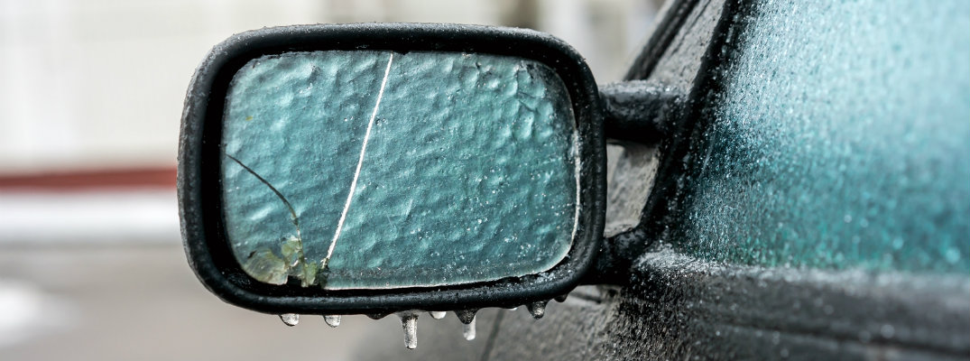 Frozen mirror and window of used vehicle in winter