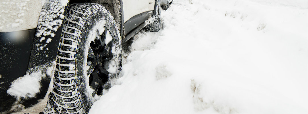 Closeup shot of vehicle tires stuck in the snow