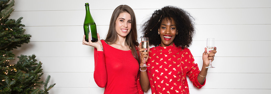 Two women holding bottles of champagne for New Year's Eve