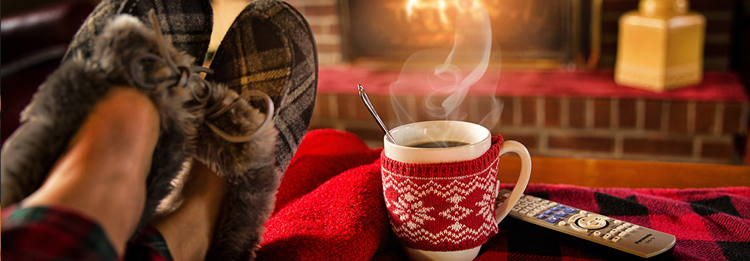 Cup of hot chocolate resting in front of fireplace
