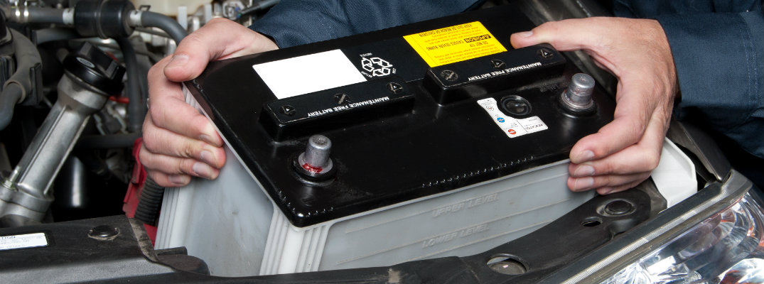 Mechanic installing new car battery in vehicle at shop