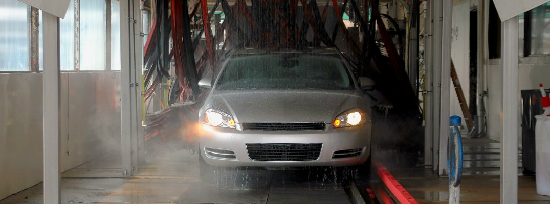 Front grille and headlights of vehicle driving through car wash