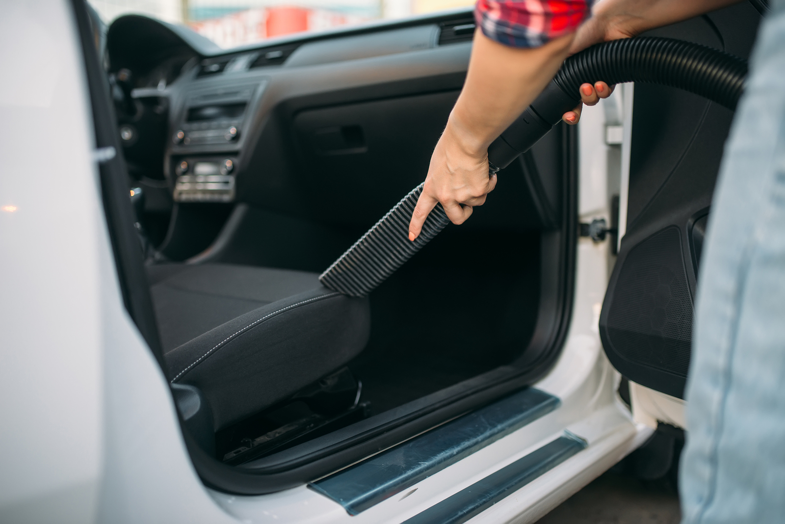 Woman cleans car interior with vacuum cleaner carvilles - How to get smoke smell out of car interior ...