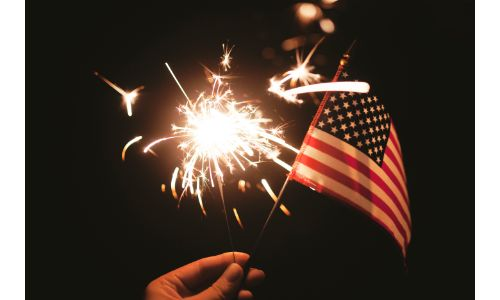 Hand holding a sparkler and flag