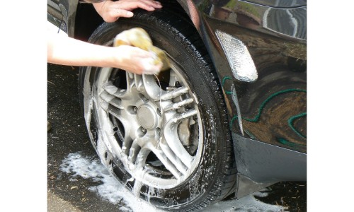 Car tire and rim being washed