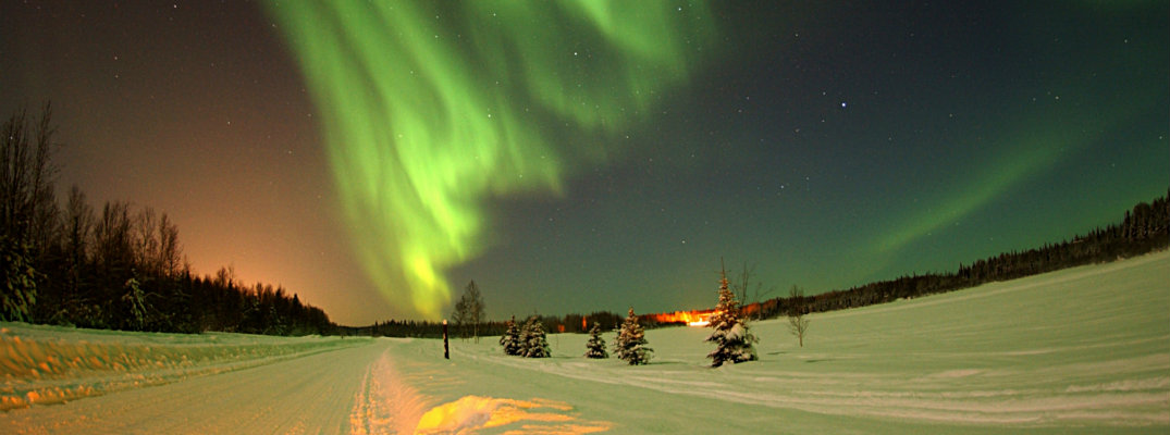 Northern Lights above a snow covered road