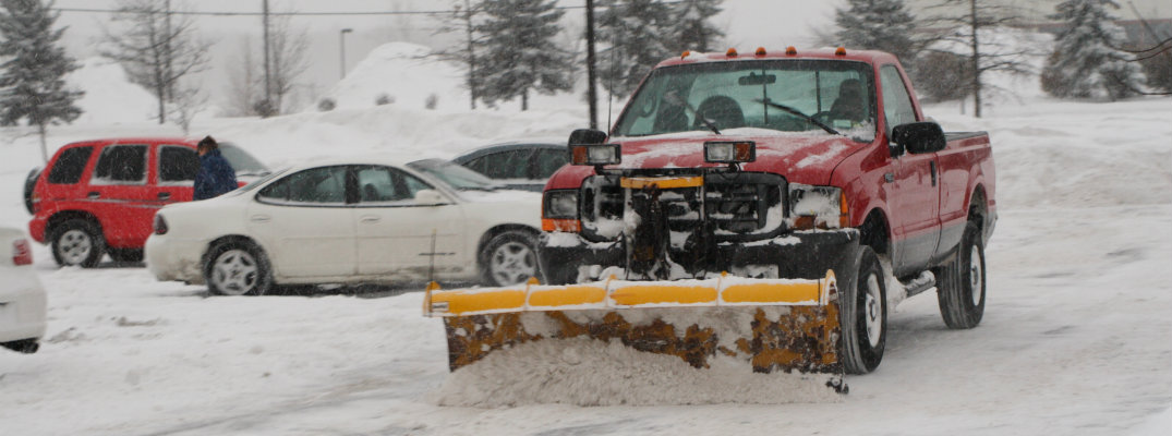 Snow plow on a truck driving down the street