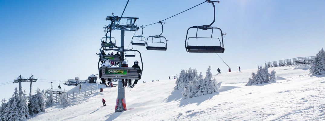 Ski lift carrying people up a mountain