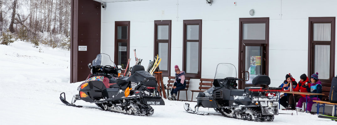 Snowmobiles gathered outside a building