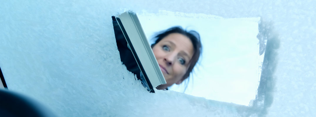 Woman scraping ice from a window