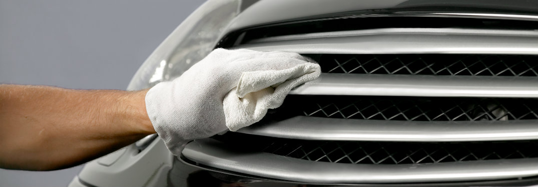 Hand wiping down a chrome bumper