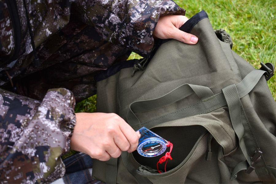 Person loading compass into backpack