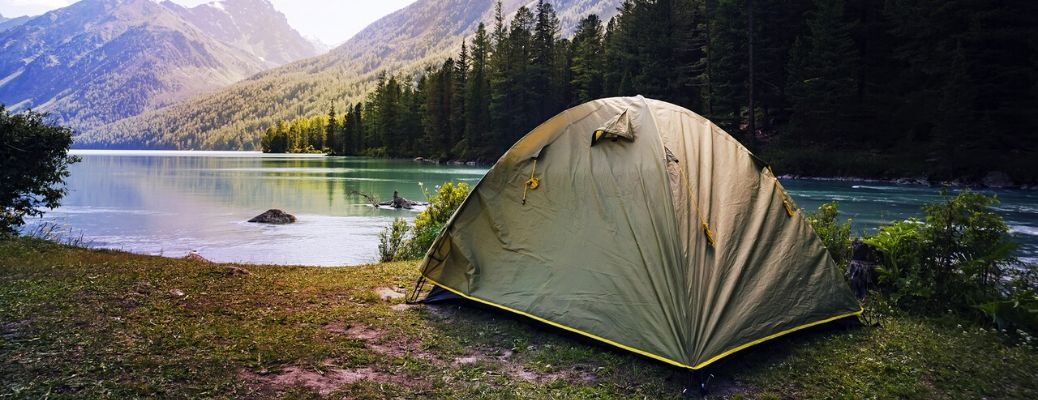 Tent pitched in front of lake and mountain range