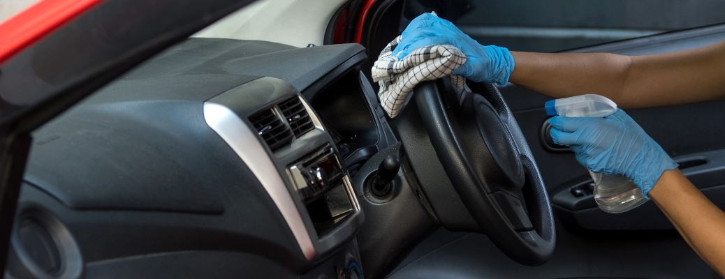 Person cleaning steering wheel of a car