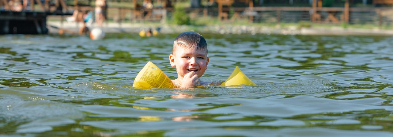 Toddler swimming in lake