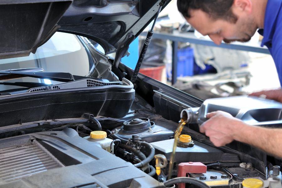 Mechanic refilling engine oil
