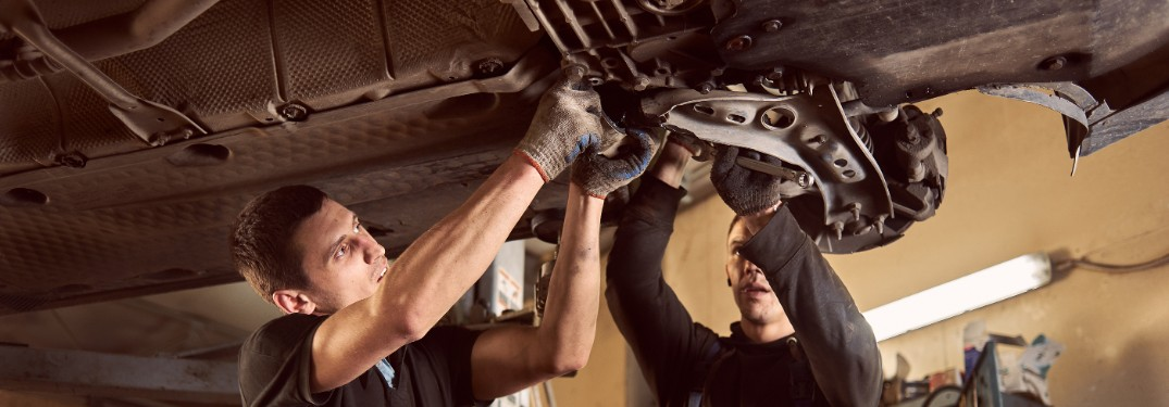 Technician and mechanic working on car