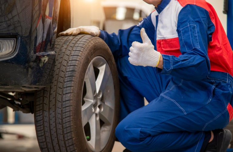 Mechanic giving thumbs up next to tire