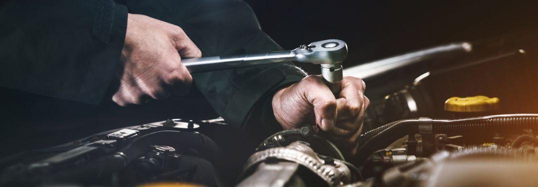 Mechanic using socket wrench on engine of car