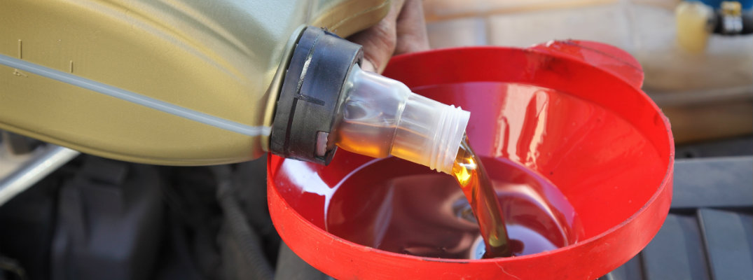 Close-up of a bottle of oil being poured into a funnel