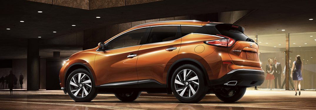 2018 Nissan Murano in orange parked in front of a window with people at a party