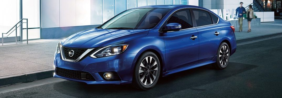 Blue 2018 Nissan Sentra parked in front of a modern building with two people walking toward it