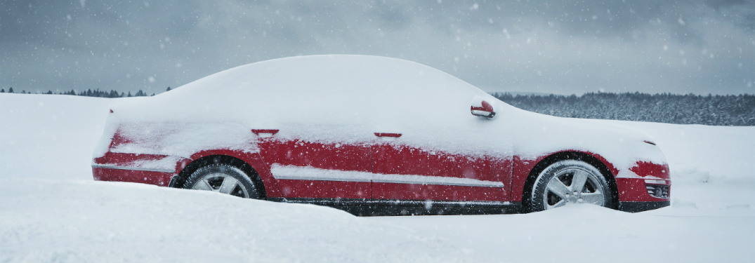 red car buried in snow on side of road