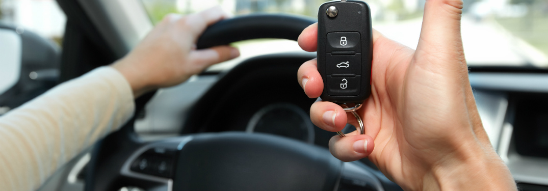 driver in car holding remote key fob