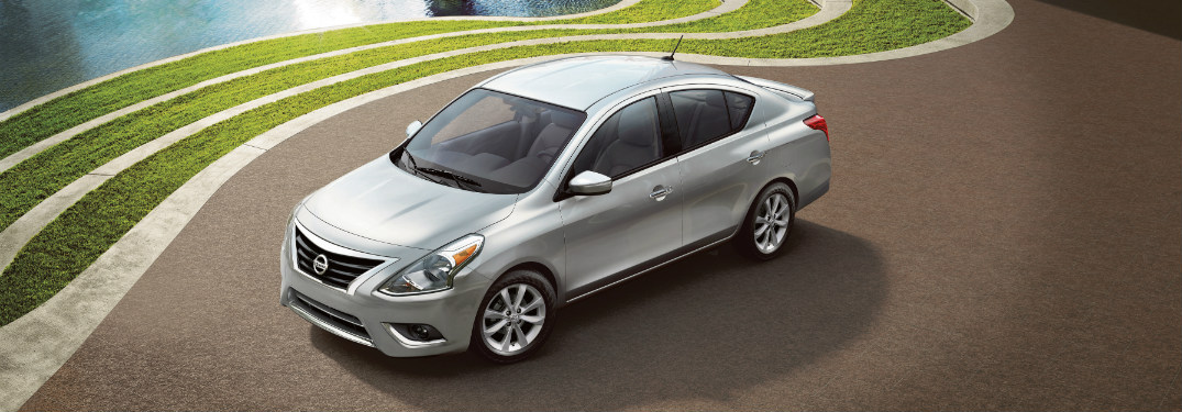 silver 2018 nissan versa parked next to grass and water