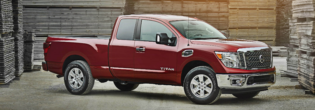 red 2018 nissan titan surrounded by stacks of wooden pallets