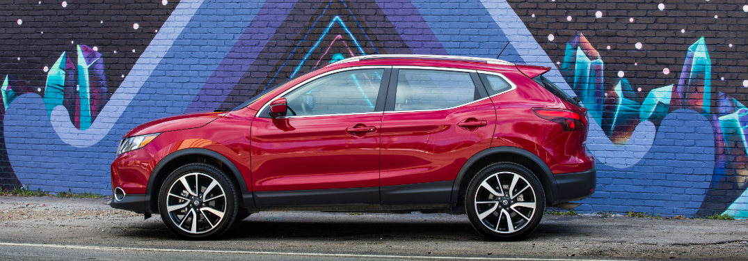 red 2018.5 nissan rogue sport side view against wall mural
