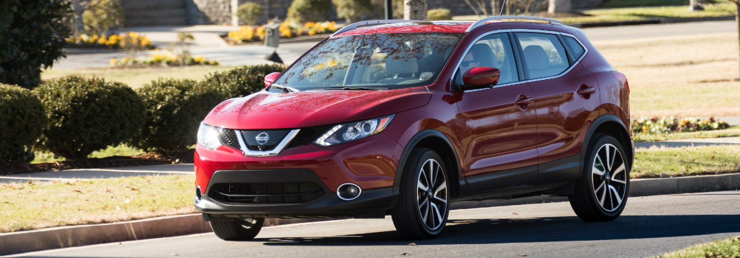 red 2018 nissan rogue sport driving on suburban road
