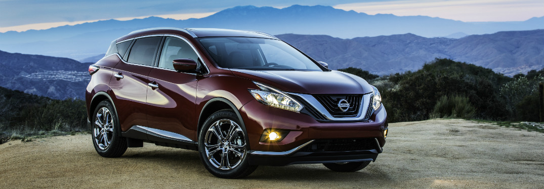 maroon 2018 nissan murano on edge of cliff with mountain range behind it