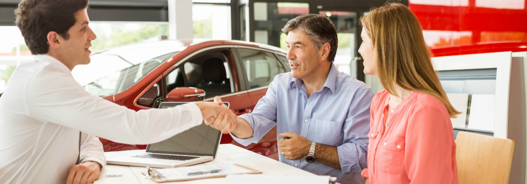 car salesperson shaking hands with couple over paperwork