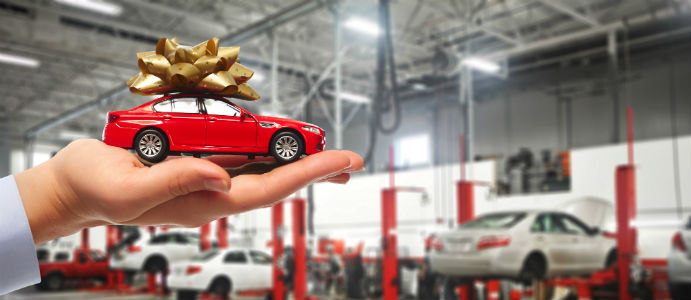car with bow on top in a hand in front of a service station