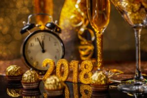 champagne and a clock next to 2018 new year's decorations