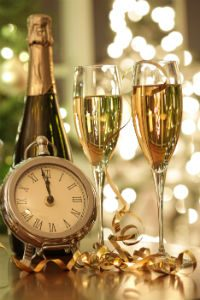 champagne and champagne flutes next to a clock with lights in the background