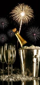 champagne in a bucket next to 2 champagne flutes with fireworks in the background