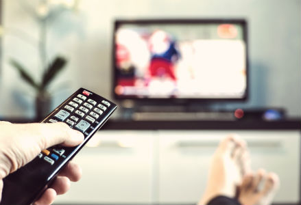 person holding a tv remote pointed at a tv